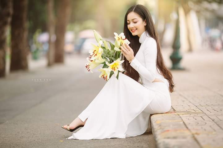 Ngồi góc ven đường, nhìn vào hoa khi chụp với áo dài (aphoto)