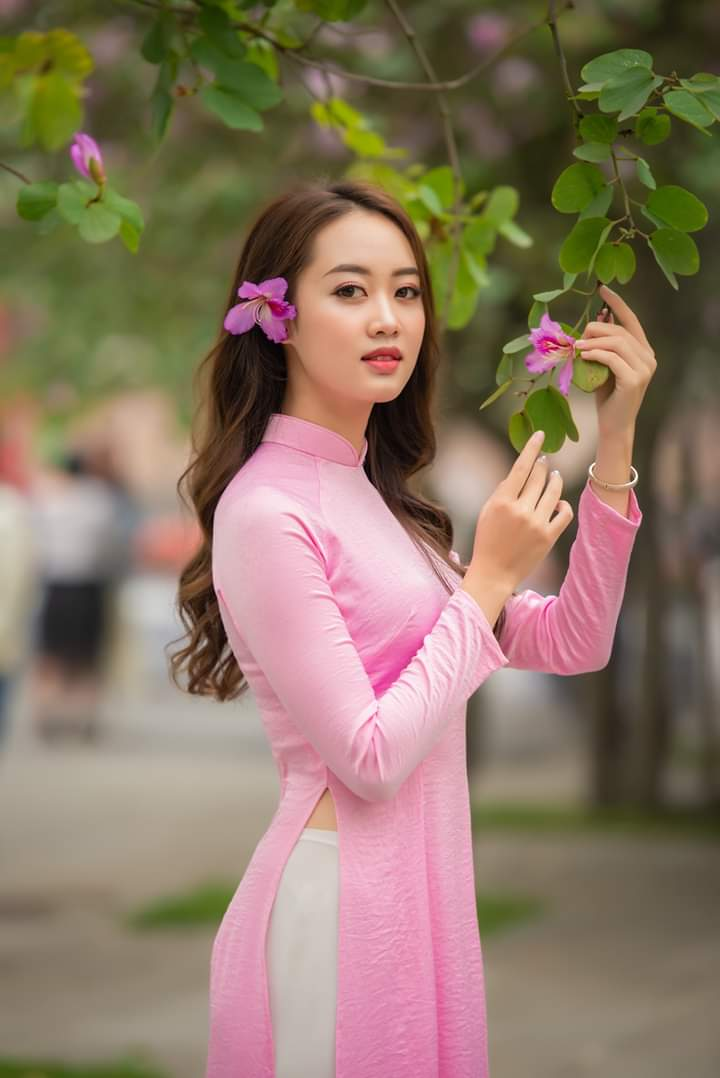 Tạo dáng áo dài với 2 tay đưa lên cầm cành hoa (Aphoto)