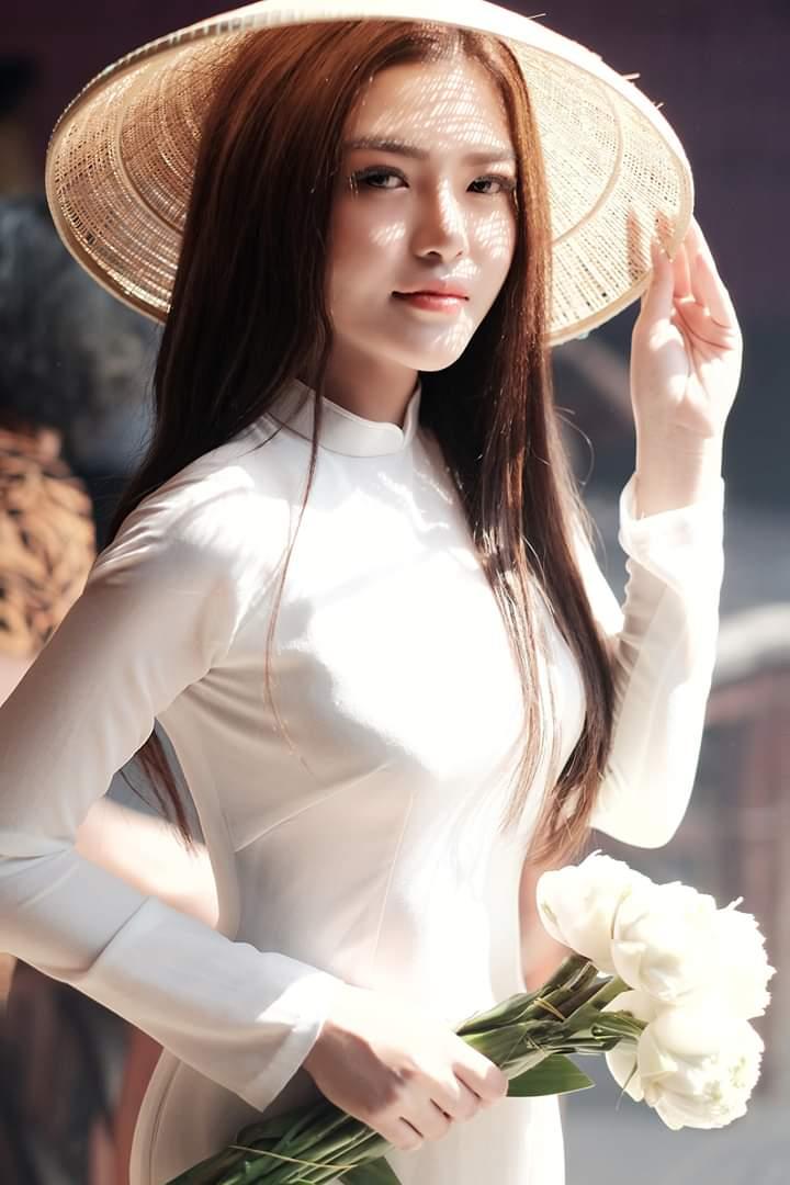 Tạo dáng áo dài với nón lá và hoa, chụp cận cảnh (Aphoto)