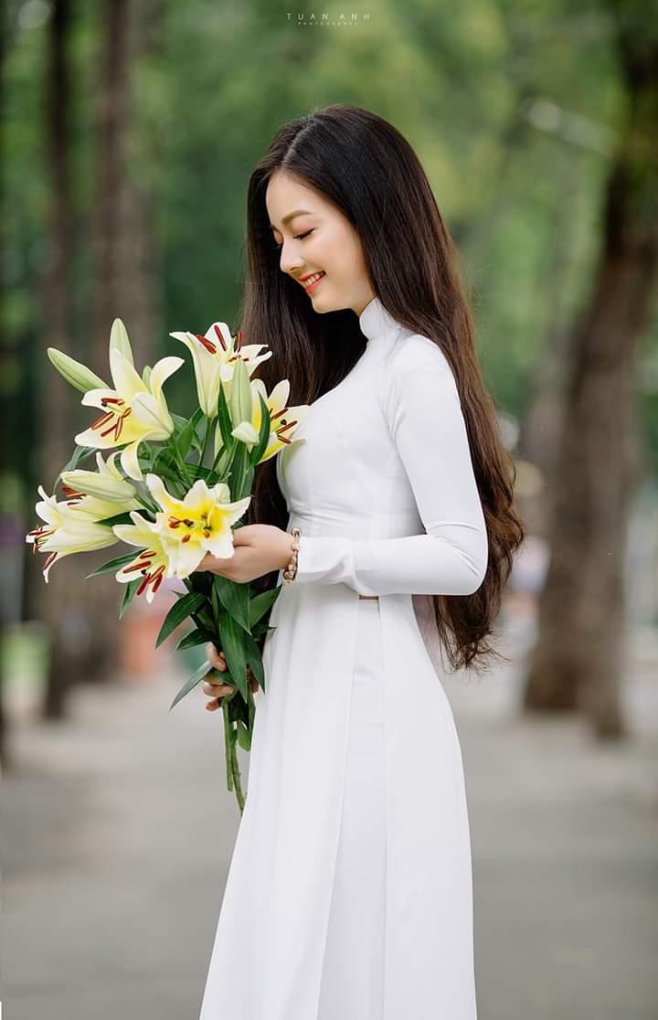 Tạo dáng với áo dài bằng cách nhìn vào hoa (Aphoto)
